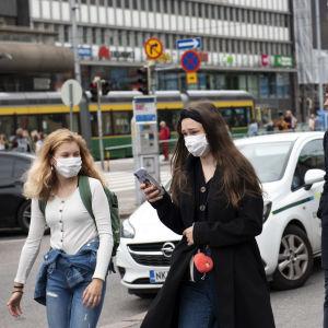 Två unga kvinnor med munskydd promenerar i centrum av Helsingfors.