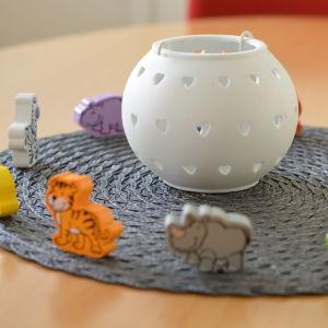 Leksaksfigurer  som föreställer djur står på ett bord, runt en vit, rund lykta