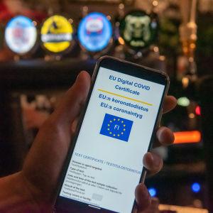 Digitalt covidintyg och telefon vid bardisk.
