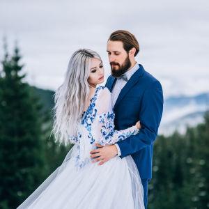 Ett brudpar poserar utomhus, brudgummen har blå kostym och bruden blå detaljer i sin vita klänning.