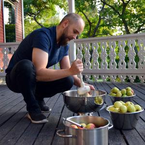 En man krossar äppel i en skål.