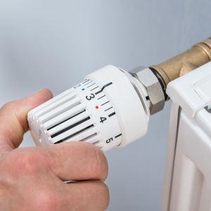En man skruvar temperaturen på ett värmeelement.