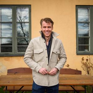 Porträtt på Rasmus Schüller framför en gammal husvägg med uteservering.