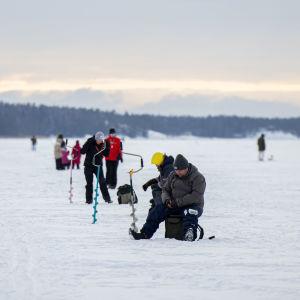 Ihmisiä meren jäällä ulkoilemassa ja pilkillä.