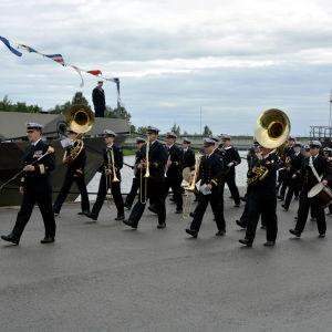 En militärmusikkår går vid en kaj med instrument i händerna.