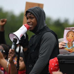 Skådespelaren John Boyega med en megafon på en antirasistisk demonstration.