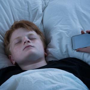 Pojke som somnat i sängen med mobiltelefon i ena handen.