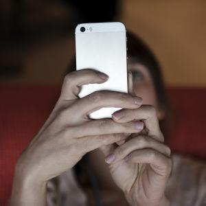 En kvinnas ansikte skymtar bakom en mobiltelefon som hon tittar på.