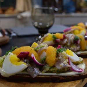 Strömmingsmackor med picklad lök och rökt majonnäs i ett kök