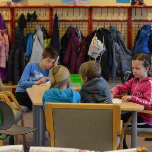 Flera barn sitter runt ett bord.