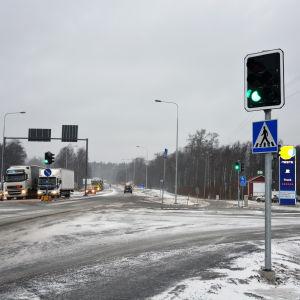 En korsning med trafikljus. Till vänster syns fordon som väntar på att få köra ut i korsningen.