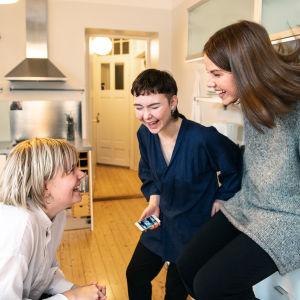 Kolme naista nauraa keittiössä, yhdellä kädessä kännykkä.