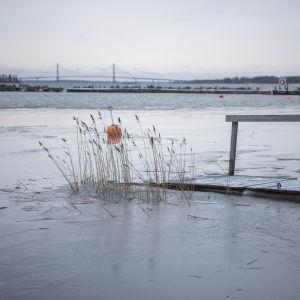 Högt vattenstånd lyfter isen upp över en brygga i Korsholms skärgård. I bakgrunden syns Replotbron.