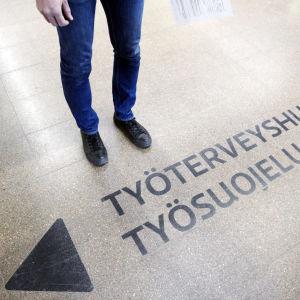 Työterveyshuolto -opastekyltti maalattuna lattiaan.