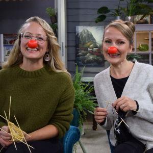 Två kvinnor med clownnäsor sitter i soffan och stickar