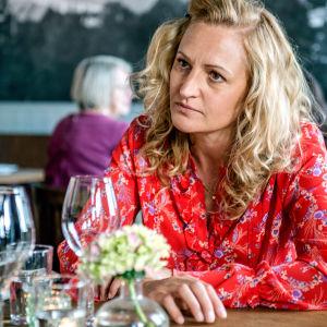 Karaktären Ella i röd skjorta i en restaurang.