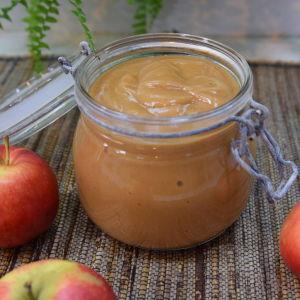 Lasipurkillinen omenasosetta pöydällä