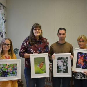 Fyra personer står i  rad med varsin fototavla framför sig. Tavlorna  är bilder fotograferade i naturen.