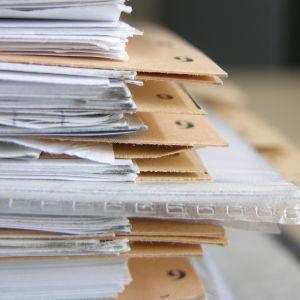Papper och mappar ligger i en hög på varandra. De är märkta med siffror.