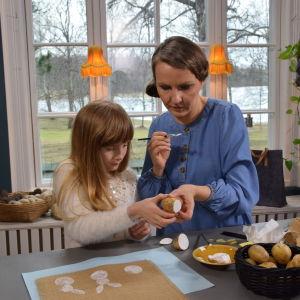 Kvinna och barn trycker tygtryck med potatis