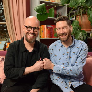 Två män ler på en soffa.