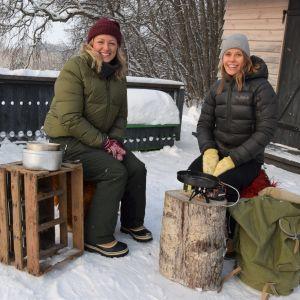 Två leende kvinnor i vintrig miljö vid ett stormkök