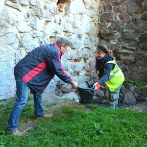 Museichef Dan Lindholm hjälper arkeolog Tarja Knuutinen vid utgrävningarna på Raseborgs slott.
