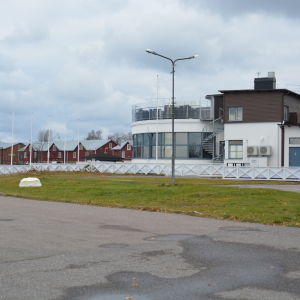 Restaurangen hsf i Hangö syns bakifrån och i bakgrunden de röda magasinen längs Hamngatan.