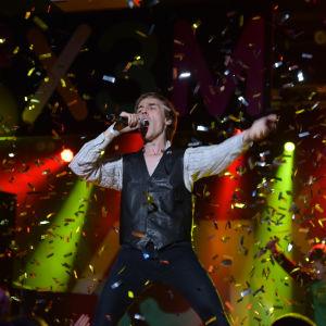 Kevin Holmström från humorgruppen KAJ står på scen i ett regn av konfetti.