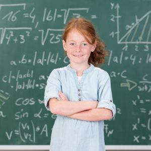 Flicka framför griffeltavla med matematiska uträkningar