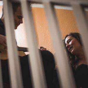"""Mies soittaa kitaraa ja nainen laulaa oranssin seinän vieressä, kuva otettu portaiden """"ristikon"""" läpi."""