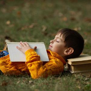 Pojke ligger på äng med en hög böcker