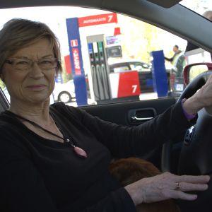 Kvinna sitter vid ratten inne i en bil.