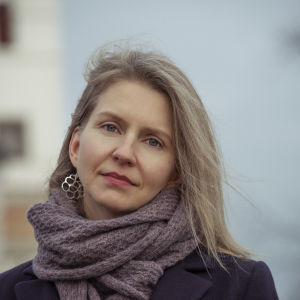 Nora Hämäläinen fotgraferad utanför tornbyggnad, vind i håret, stor grå halsduk.