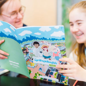 Kaksi hymyilevää oppilasta lukee Yrityskylän opaskirjasta