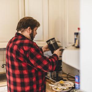 Mies flanellipaidassa keittää kahvia, kaataa kahvinpapuja keittimeen.