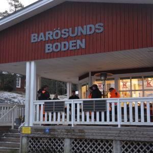 Ett rött hus, Barösundsboden, som är en bybutik. Folk står utanför huset på en takförsedd stor altan
