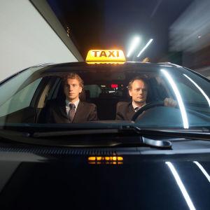 Taksikujettaja ja etupenkillä istuva matkustaja edestä kuvattuna