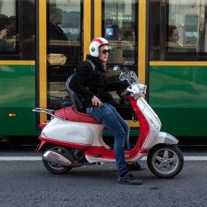 Ung man med moped och spårvagn i bakgrunden.