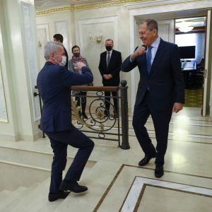 Pekka Haavisto och Sergej Lavrov armbågshälsar i trappan.