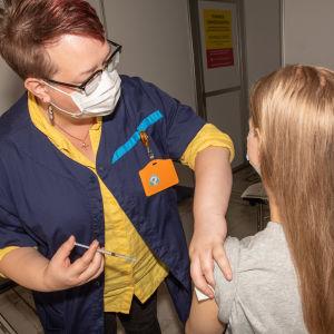 Sairaanhoitaja Niina-Liisa Åhs antaa rokoten potilalle Helsingin Messukeskuksessa.