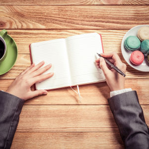 Händer i beråd att skriva i en anteckningsbok
