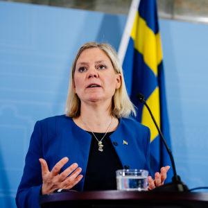 Sveriges finansminister Magdalena Andersson framför en Sverigeflagga.