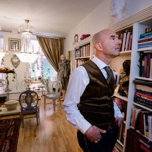 Mark Levengood framför sin överfulla bokhylla.