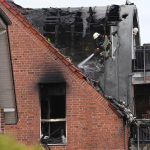 Palomies sammuttaa rakennusta, jonka katossa on suuri reikä.