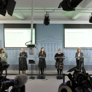 Partiledarna för partierna i Sanna Marins regering, plus finansminister Matti Vanhanen, står på rad under regeringens presskonferens.