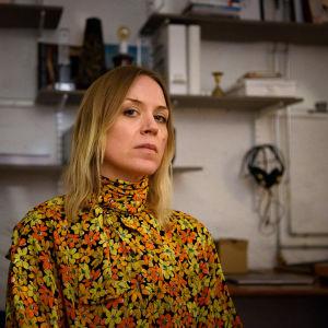 Kvinna tittar rakt in i kameran, bakom finns arbetsrummet med hylla.