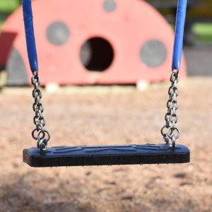 En gunga hänger i en lekpark.