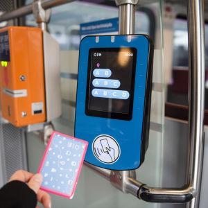 Ett resekort som hålls upp mot avläsaren på ett lokaltåg.