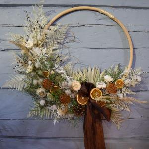 En krans med dekoraitoner av torkade blad och blommor i ljusbeigea toner.